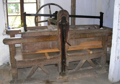 room-size wooden frame with rock-filled box over 2 rollers