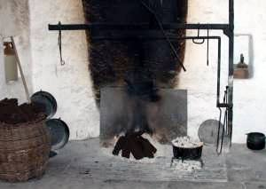 Peat sods on open hearth in wide chimney space, fire-making and cooking equipment